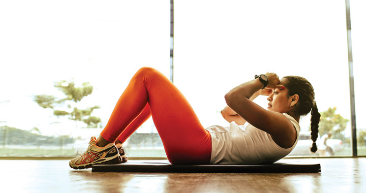 Woman in front of window doing a sit up on a yoga mat